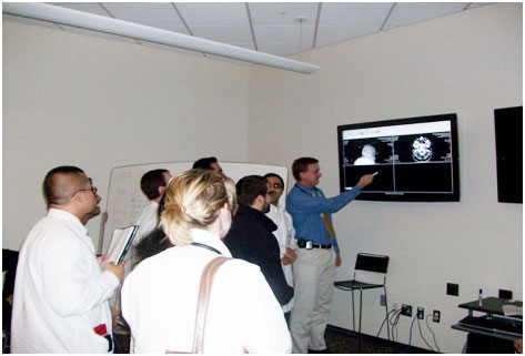 Residents reviewing CT scans on monitor