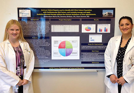 two Internal Medicine residents presenting poster