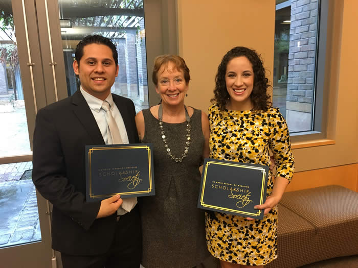 two students with mentor holding awards