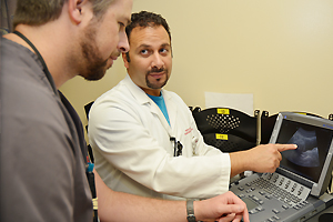Faculty with resident viewing ultrasound